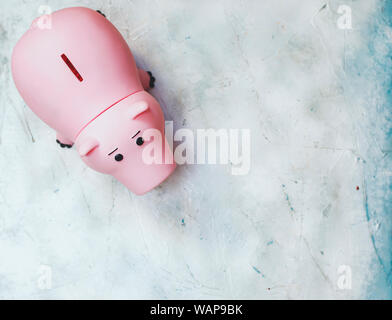 A pink piggybank from above with a large copy space