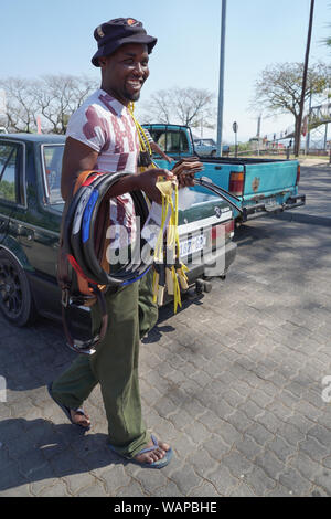 black African man person street vendor salesman selling various items in a parking lot in Hazyview, Mpumalanga, South Africa - Stock Photo