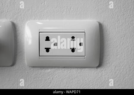 White universal electricity sockets plug on a white wall - Stock Photo