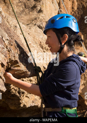 Close up of first time technical climber finding hand holds in rock face as she climbs for the first time. - Stock Photo