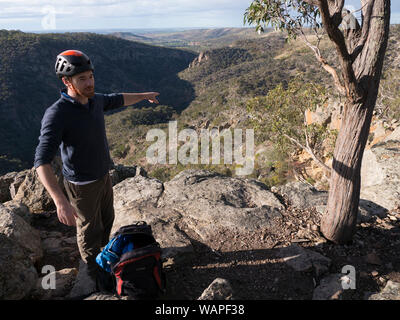 Technical climbing instructor pointing out rock face and gorge entrance where new students will experience climbing for the first time. - Stock Photo