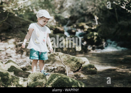 Adorable little girl playing the river in summer, with a cap and shorts. - Stock Photo