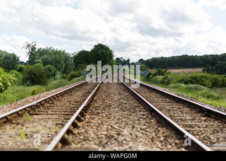 An empty train track, there are 2 tracks leading to a point on the horizon in rural countryside - Stock Photo