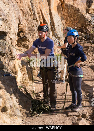 Technical climbing teacher showing beginner student how to use rope properly and where to place hands when climbing for the first time. - Stock Photo