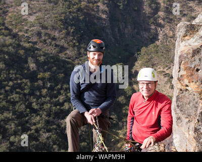 Technical climbing instructor and new student, standing on cliff edge, smiling at camera before abseiling for the first time. - Stock Photo