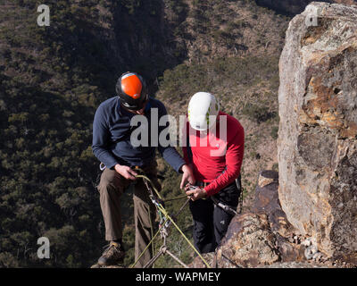 Technical climbing instructor showing first time climber how to tie in and place hands on rope before first abseiling experience. - Stock Photo