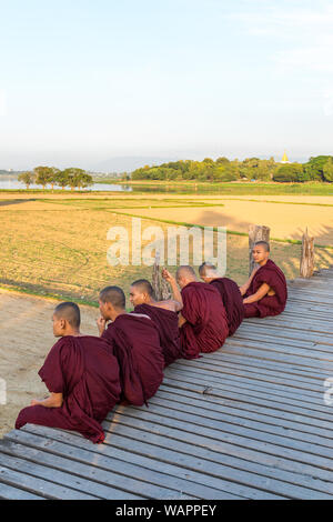 MANDALAY, MYANMAR - 03 DECEMBER, 2018: Vertical picture of burmese buddhist monks sitting on the wooden U Bein Bridge, which is a touristic attraction - Stock Photo