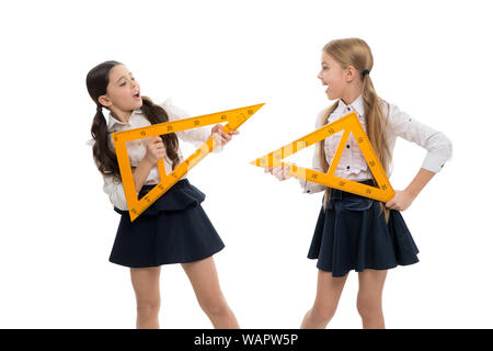 A lesson for the future. Small children with measuring instruments at school lesson. Little girls preparing for geometry lesson. Cute schoolgirls holding triangular rulers for lesson. - Stock Photo