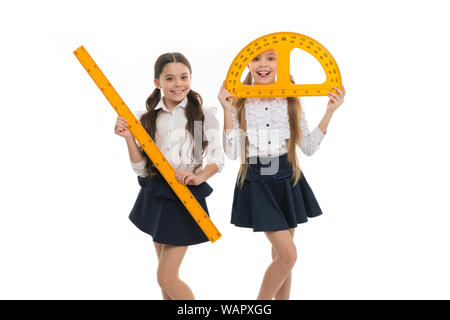 Geometry lesson is much fun. Little girls holding protractor and ruler for lesson. Small children with measuring instruments at school lesson. Cute schoolgirls preparing for geometry lesson. - Stock Photo
