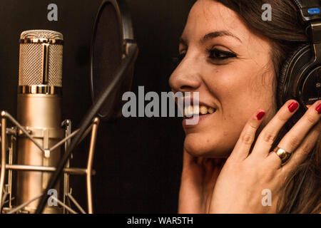 Portrait of a beautiful girl using a condenser microphone in a recording studio or radio station - Stock Photo