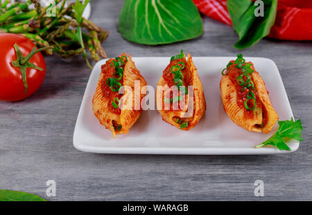 Pasta jumbo shells stuffed with minced beef meat and tomato sauce on a plate. - Stock Photo