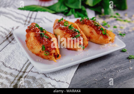 Shells pasta stuffed with a ricotta cheese, meat and basil leaves. - Stock Photo