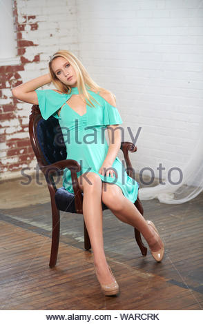 Beautiful blonde young woman (model) poses in studio wearing teal dress - seated in vintage chair - Stock Photo