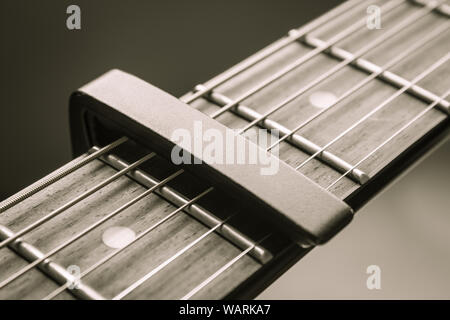 Black Capo on Acoustic Guitar String and Fingerboard with Soft Natural Light in Close up View Stock Photo