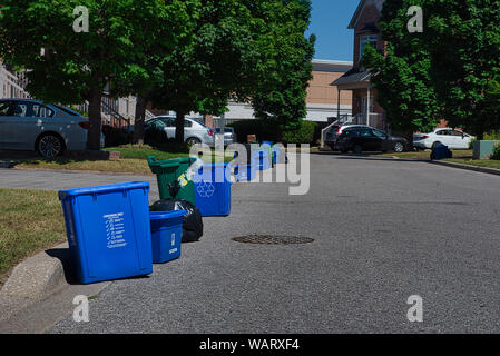 Garbage, recycling and food waste bins are waiting to be picked up in front of  houses on garbage day. - Stock Photo