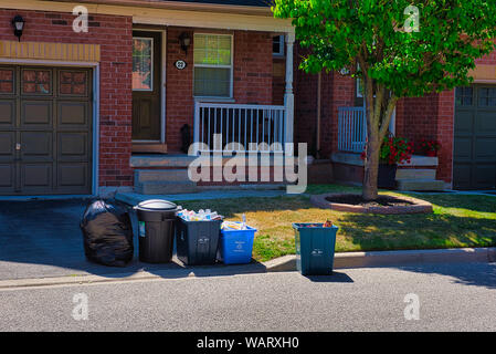 Garbage, recycling and food waste bins are waiting to be picked up in front of a house on garbage day. - Stock Photo