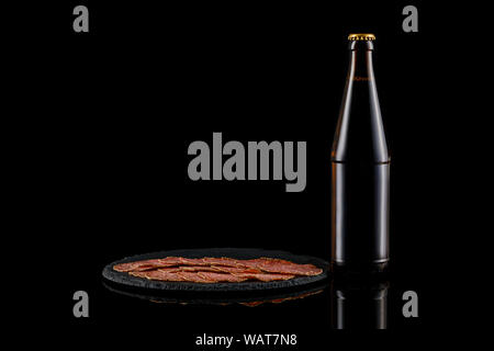 glass beer bottle and delicious sliced sausages on stone boardon black background. copy space - Stock Photo