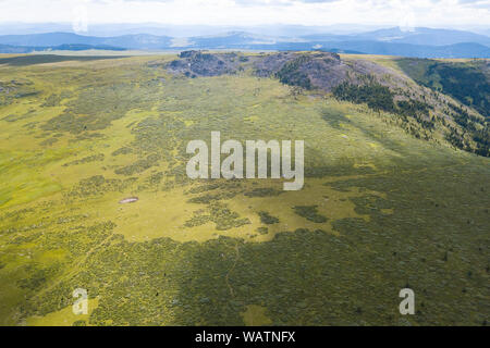 landscape of the ridge covered with green trees and view a valley flooded with sunlight ,pasture, with dense clouds in the sky. summer day in the moun - Stock Photo