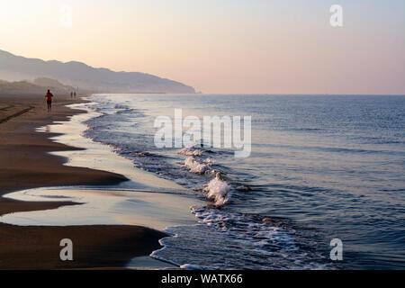 Unidentified man jogging in orange sportswear on sandy beach on sinrise over sea or ocean, seascape - Stock Photo