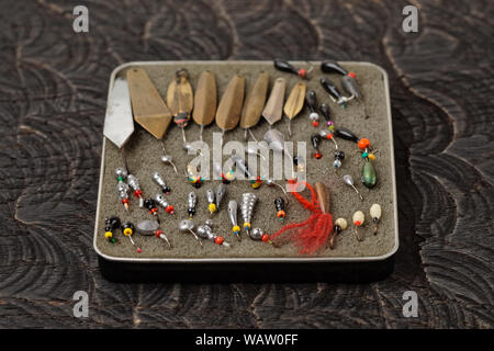 Set of lures for ice fishing on black wooden surface - Stock Photo
