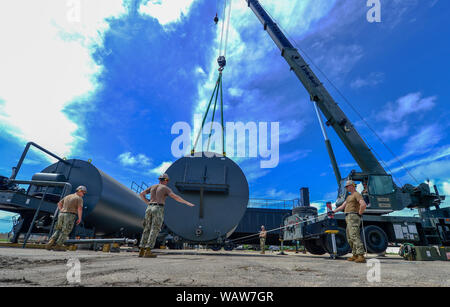SANTA RITA, Guam (Aug. 20, 2019) Seabees assigned to Naval Mobile Construction Battalion (NMCB) 4 assemble a portion of an asphalt batch plant at Naval Base Guam. NMCB-4, provides expeditionary construction and engineering capabilities that includes maintenance and operation of expeditionary bases and facilities, tactical sustainment bridging, humanitarian assistance through construction civic action details and theater disaster response capabilities in the U.S. 7th Fleet area of operations. (U.S. Navy photo by Mass Communication Specialist 1st Class Billy Ho) - Stock Photo