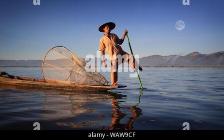 One leg paddling fisherman on a traditional boat at sunrise, Inle Lake, Burma (Myanmar) - Stock Photo