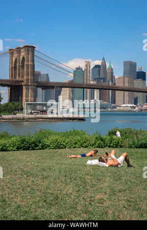 Brooklyn summer, view of men sunbathing in Main Street Park, Brooklyn, with the Brooklyn Bridge and Lower Manhattan skyline in the distance, NYC, USA - Stock Photo
