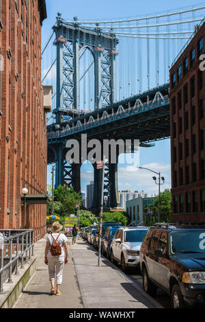 Dumbo Brooklyn, rear view of a mature woman approaching the Manhattan Bridge in Washington Street in the Dumbo area of Brooklyn, New York City, USA. - Stock Photo