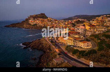 Colorful houses on the hillsides with a fortress on the top. Aerial view of popular travel destination of medieval town Castelsardo, Sardinia, Italy. - Stock Photo