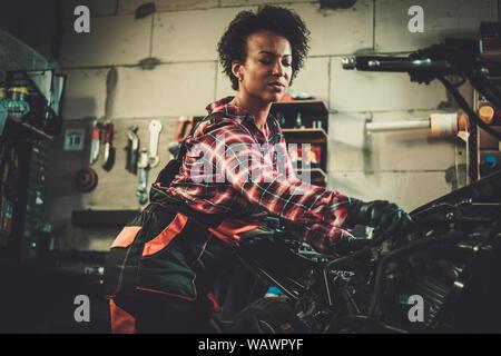 African american woman mechanic repairing a motorcycle in a workshop.