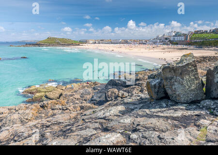 St Ives in West Cornwall, England. Wednesday 21st August 2019. UK Weather: Holidaymakers enjoy a day of warm sunshine and a gentle breeze at Porthmeor - Stock Photo