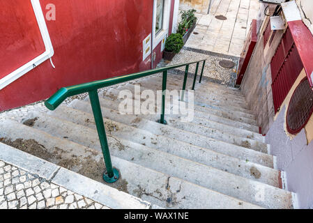 Staircase in traditional paving stones with green railing leading down to paving stone alley between colourful building walls in Cascais Portugal - Stock Photo