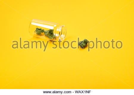 Dried medical marijuana buds in a small open glass jar and scattered aside on yellow background. Alternative treatment. Medical cannabis.Place for tex - Stock Photo