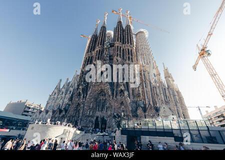 BARCELONA, SPAIN - AUGUST 10, 2019: Sagrada Familia building exterior on hot summer day in Barcelona Spain with blue sky - Stock Photo