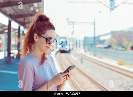Young woman using her cell phone on subway platform, checking message sms e-mail or train schedule. Girl texting on smartphone while city train approa