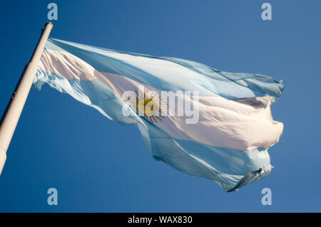 Argentinian flag waving on a sunny day against the blue sky en Buenos Aires Argentina - Stock Photo