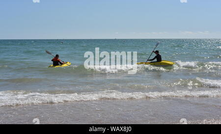 Boscombe, Bournemouth, Dorset, England, UK. 22nd Aug, 2019. Weather: Warm and sunny afternoon on the south coast beach with temperatures rising into the bank holiday weekend accompanied by a good dose of late summer hot sunshine. Two kayakers take to the water. Credit: Paul Biggins/Alamy Live News - Stock Photo
