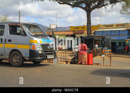 Woman selling at market stall at side of road in small village, Kenya, East Africa. Typical small shops including one called 'Dads pub' - Stock Photo