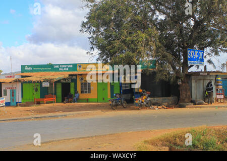 Village street, Kenya, East Africa. Local people outside small shops under blue skies. Authentic Africa, travel by Road - Stock Photo