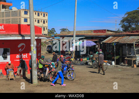 Group on men on motorbikes outsside small shops at side of road in Kenya, East Africa. Blue sky sunny day. Typical mode of transport in Kenya - Stock Photo