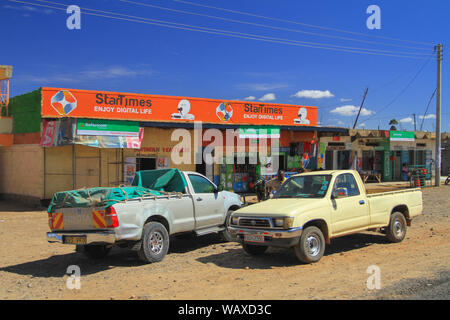Cars outside small shops at side of road Kenya, East Africa. Blue skies. Authentic Africa, travel by Road. Typical dirt road surface - Stock Photo