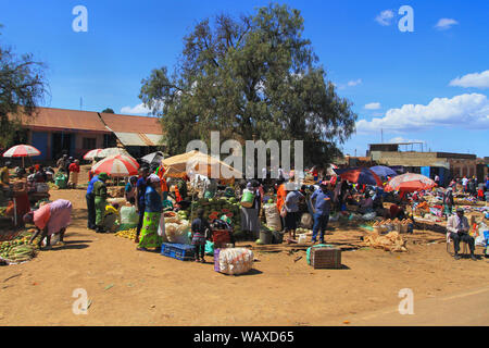 Fruit and vegetable market Kenya, East Africa. Local people buying and selling produce at side of road under sun parasols - Stock Photo