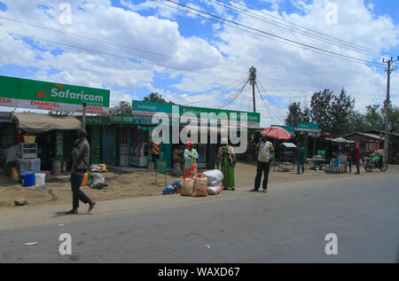 Village street, Kenya, East Africa. Local people outside small roadside shops including 'Safaricom' phone and internet access - Stock Photo