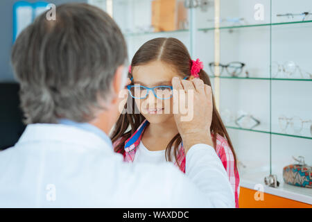 Pleasant cute girl trying on new glasses - Stock Photo