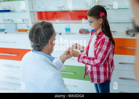 Cute nice girl choosing between different eyeglasses - Stock Photo