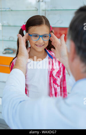 Cheerful positive girl wearing glasses in blue frame - Stock Photo