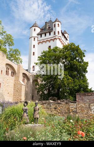 Eltville Electoral Castle with a bronze statue of a biedermeier couple in the rose garden below - Eltville am Rhein, Germany - Stock Photo
