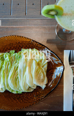 Thai food on dinner table, stir fried fresh cabbage with fish sauce in vinatge glass plate on wood table with Kiwi smoothie - Stock Photo