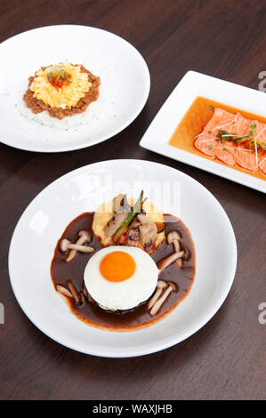 Japanese spicy Tan Tan pork over rice, salmon tataki salad and hamburger steak with sunny side up egg and mushroom. Top view shot - Stock Photo