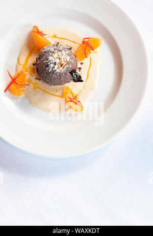 French dessert. Chocolate fondant lava cake with vanilla sauce, citrus and gold leaf on white plate top view - Stock Photo